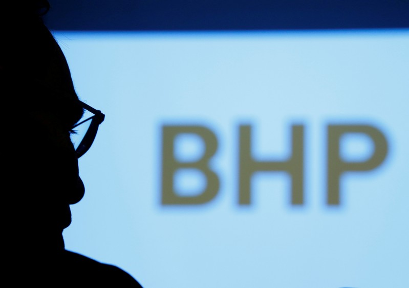 FILE PHOTO: A BHP executive is silhouetted against a screen projecting the company's logo.