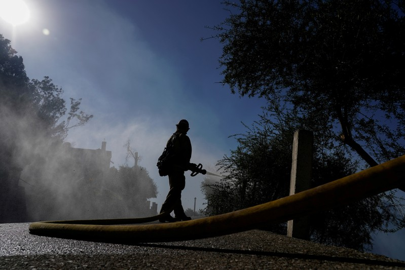 FILE PHOTO: A firefighter tackles the Dexter fire on a hillside near Riverside
