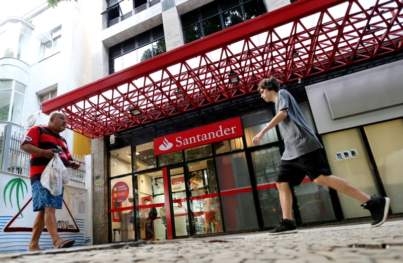 FILE PHOTO: People walk past a Banco Santander branch in Rio de Janeiro