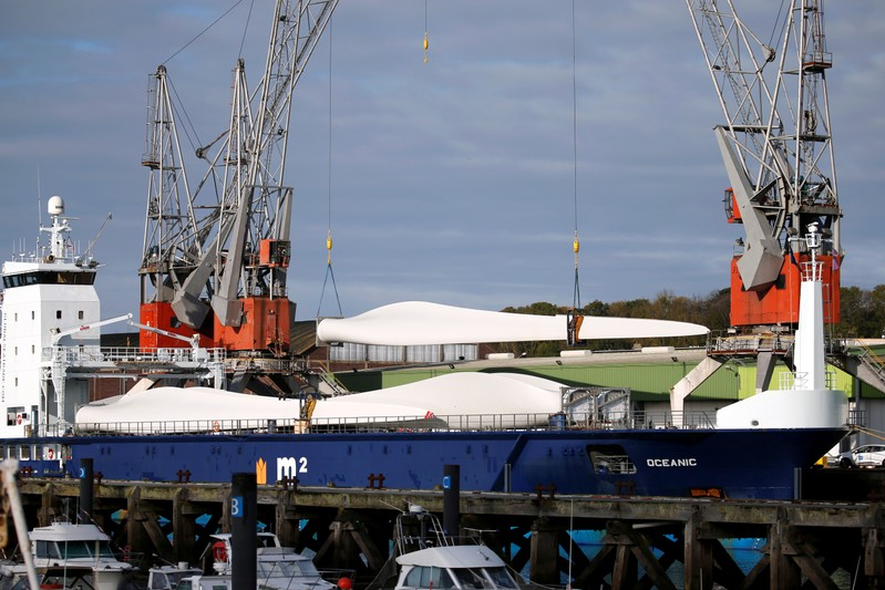 Cranes unload wind turbine blades from a ship in the port of Dieppe,