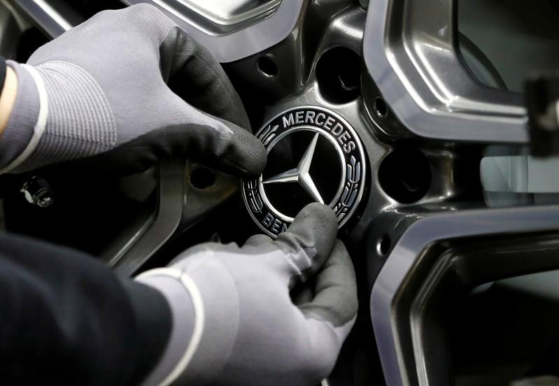 FILE PHOTO: An employee of German car manufacturer Mercedes Benz installs a hubcap at a A-class