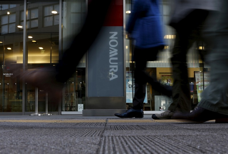 FILE PHOTO: Pedestrians walk past a signboard of Nomura Securities outside its branch in Tokyo