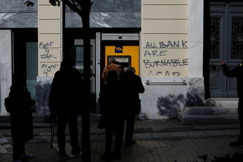 FILE PHOTO: People line up at an automated teller machine outside a Piraeus Bank branch in