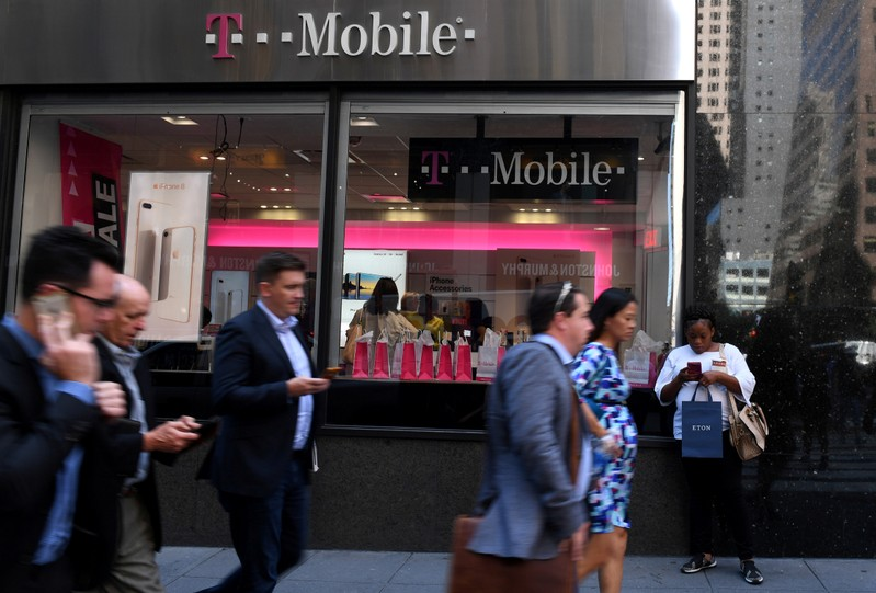 Pedestrians use their smart phones as they pass a T-Mobile retail store in New York City