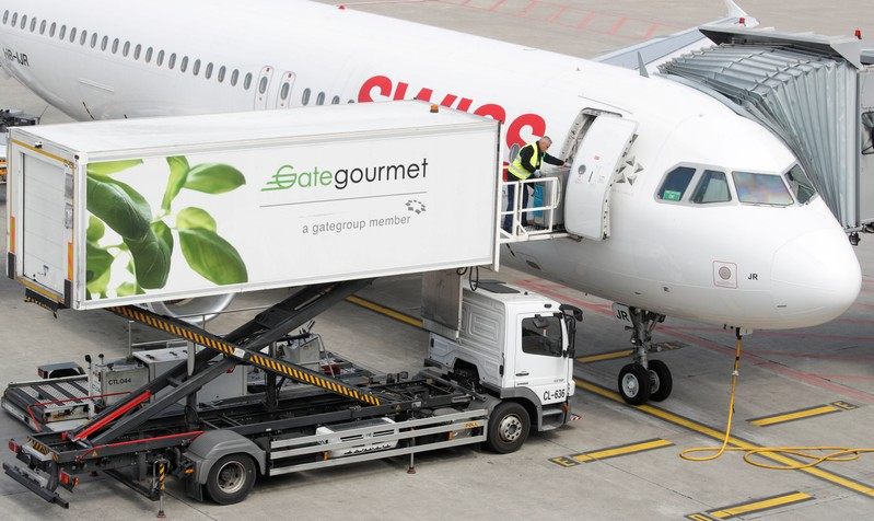 FILE PHOTO: Gate Gourmet staff loads a trolley aboard an Airbus A320-214 of Swiss airlines at