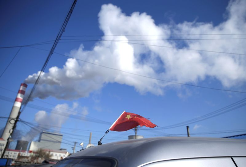 A Chinese flag is seen on the top of a car near a coal-fired power plant in Harbin