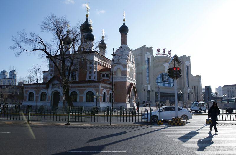 A man runs near an Orthodox church on a cold winter day in Harbin