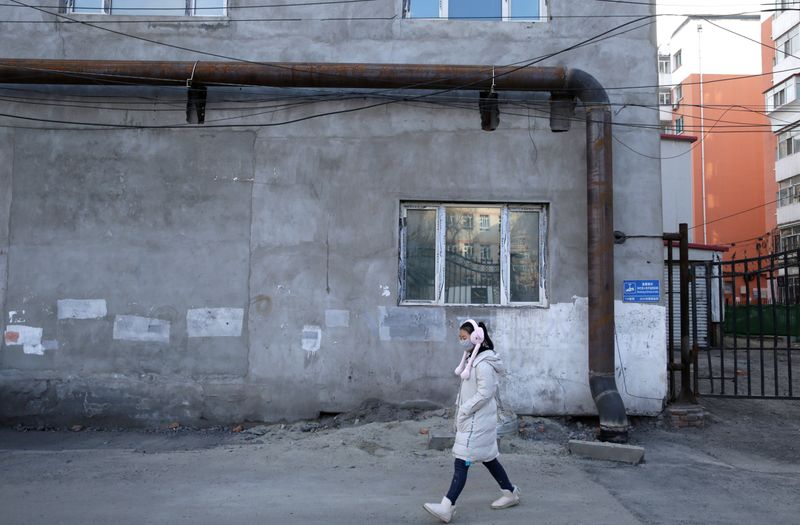 A woman walks past the gas pipeline settled into an old heating station, which is being changed