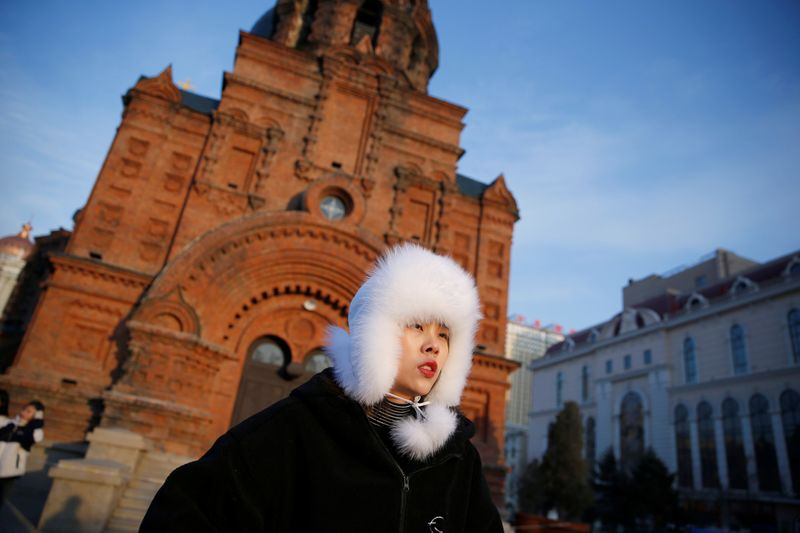 A woman stands in front of the Saint Sophia Cathedral in Harbin