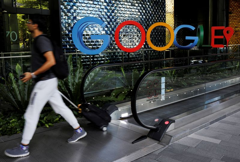 FILE PHOTO: A man passes a Google signage outside their office in Singapore