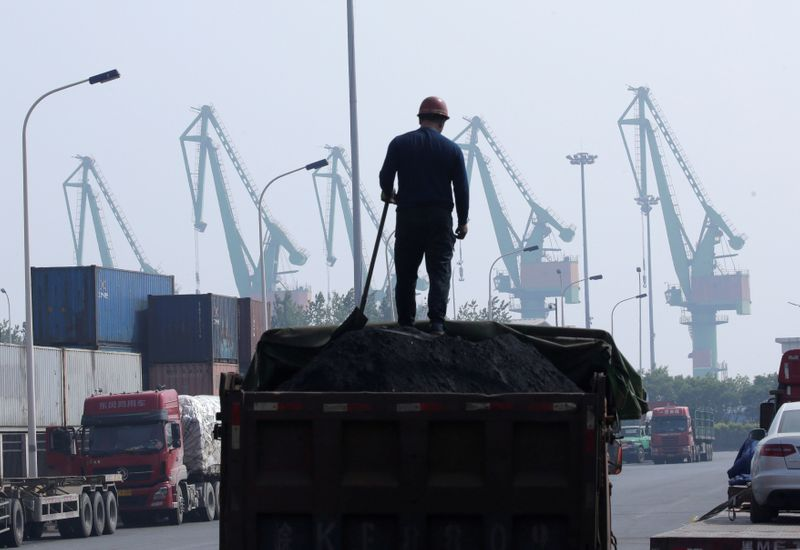 FILE PHOTO: A labourer loads coal in a truck next to containers outside a logistics center near