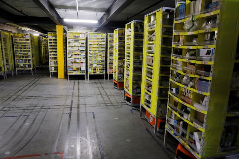 Tracks are left on the floor showing where robots carry shelves full of items inside of an
