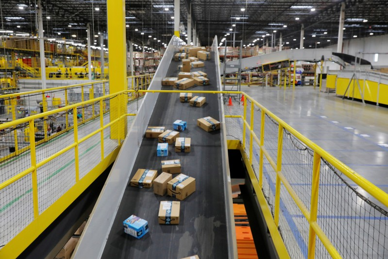 Amazon packages are transported by conveyor belts inside of an Amazon fulfillment center on