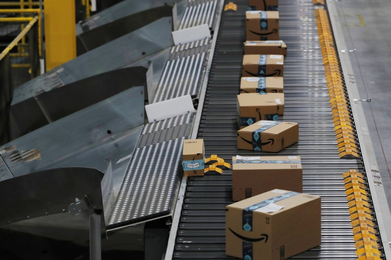 Amazon packages are pushed onto ramps leading to delivery trucks by a robotic system as they