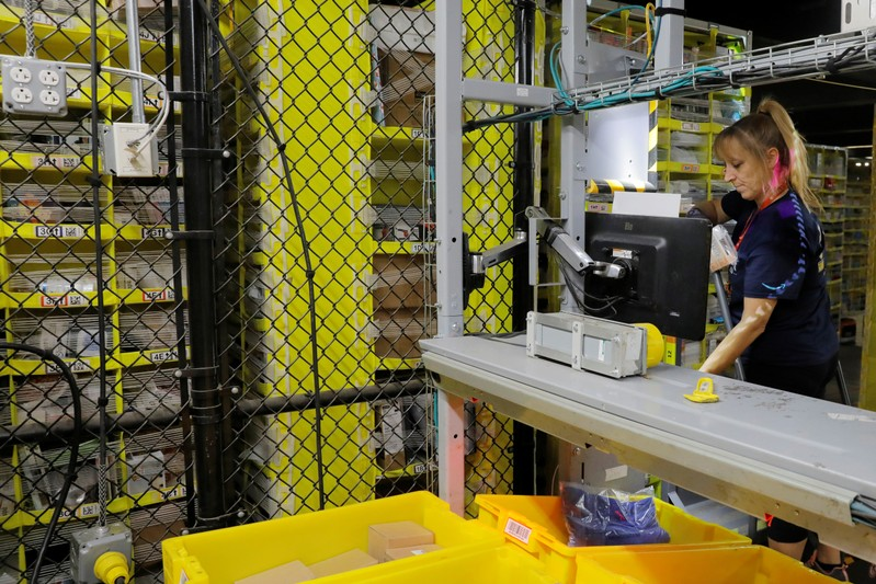 An Amazon employee works to stow items inside of shelves delivered by robots inside of an