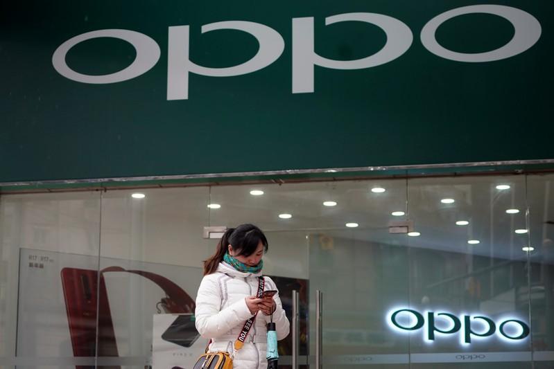 A woman walks by an Oppo logo at a shopping mall in Shanghai
