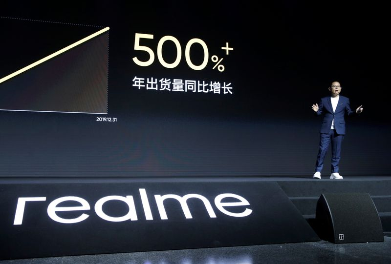Man looks at mobile phone next to Realme logo during product launch event of X50 5G in Beijing