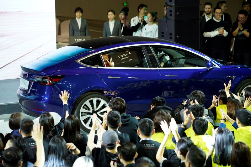 Tesla Inc CEO Elon Musk takes off his coat onstage during a delivery event for Tesla China-made