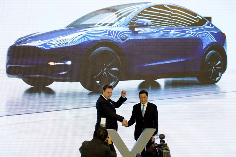 Tesla Inc CEO Elon Musk speaks next to a screen showing an image of Tesla Model 3 car during an