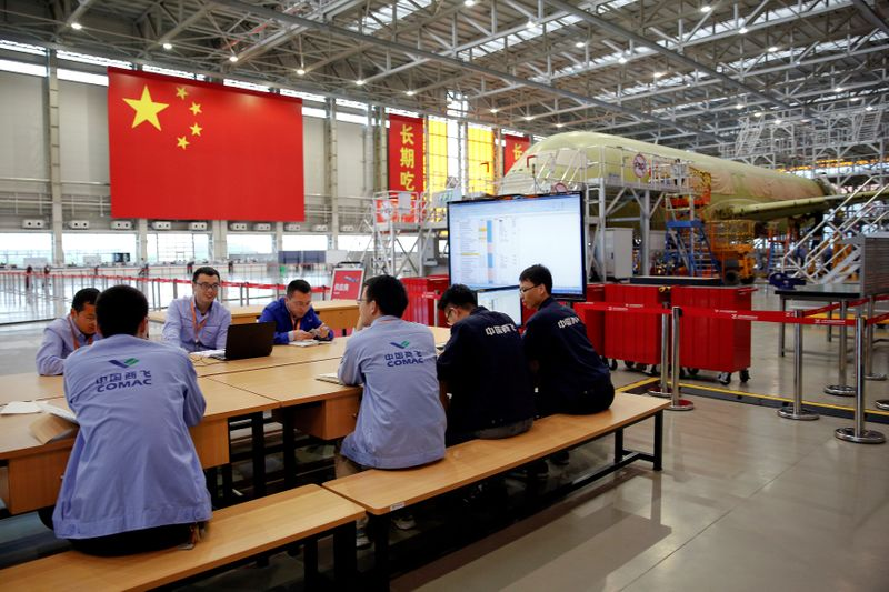 FILE PHOTO: Employees work on a China's home-grown C919 passenger jet at Manufacturing and