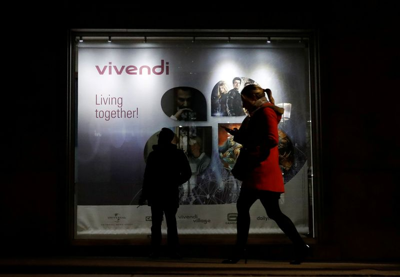 FILE PHOTO: A man stands as a woman walks past a sign of Vivendi at the main entrance of the