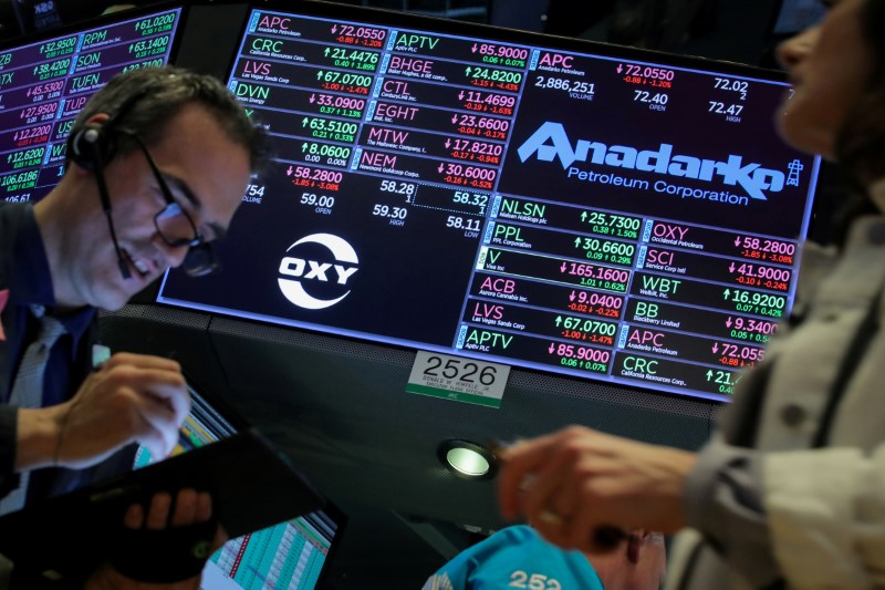 FILE PHOTO: Traders work on the floor by the post that trades Anadarko Petroleum and Occidental