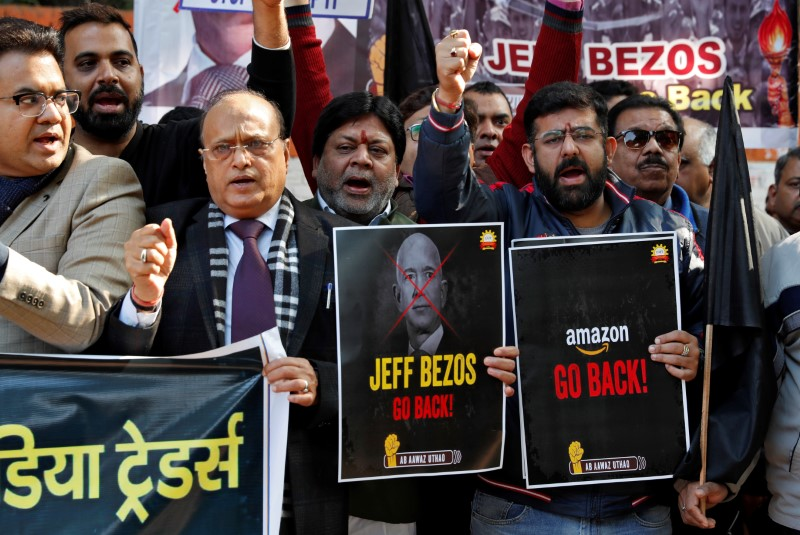 Members of the Confederation of All India Traders hold placards during a protest against the