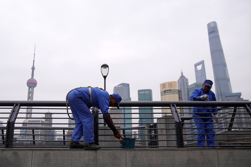 Workers paint at the Bund in front of Lujiazui financial district of Pudong, Shanghai