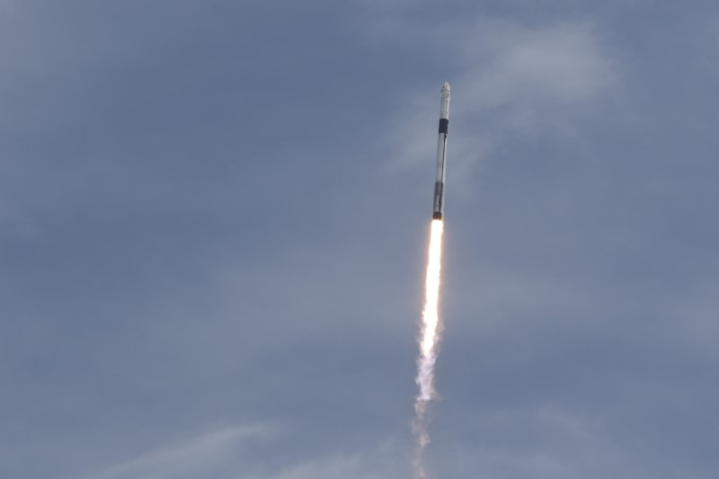 A SpaceX Falcon 9 rocket, carrying the Crew Dragon astronaut capsule, lifts off on an in-flight