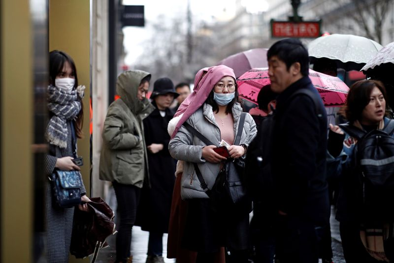 Tourist wears a protective mask at a duty free shop in Paris as the country is hit by the new