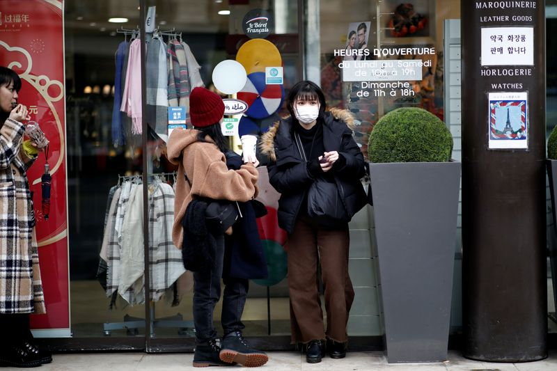Employee of an empty duty free shop is pictured in Paris as the country is hit by the new