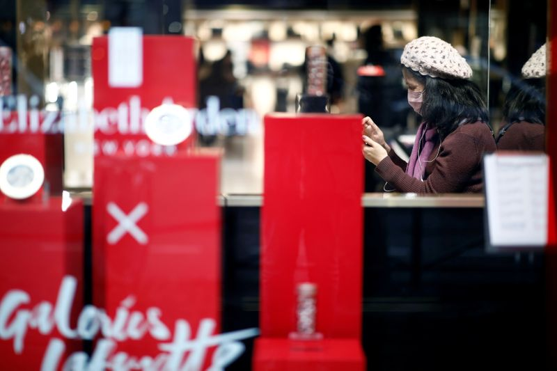 Tourist wears a protective mask as she looks at her mobile phone at the Galeries Lafayette