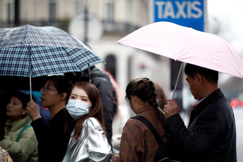 Tourist wearing protective masks enter a duty free shop in Paris as the country is hit by the