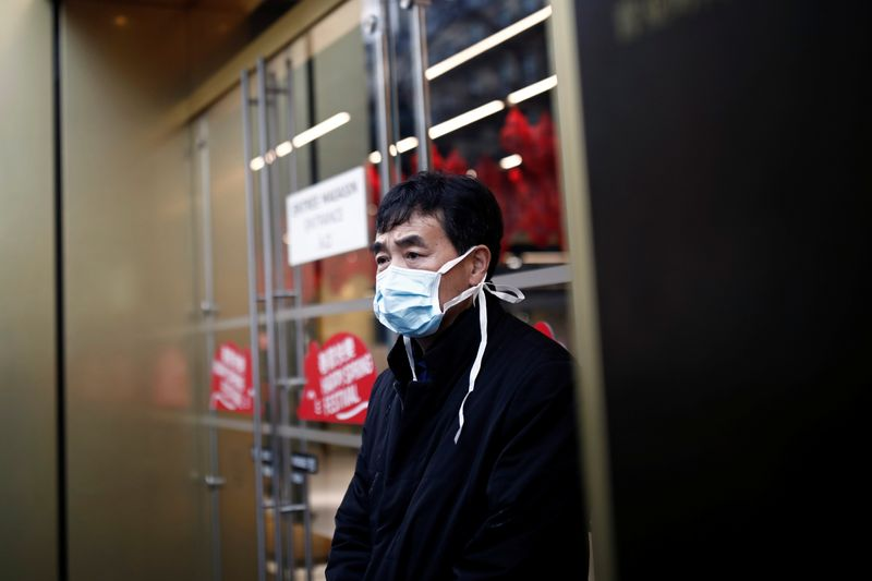 Tourist wears a protective mask in front of the Galeries Lafayette department store in Paris as