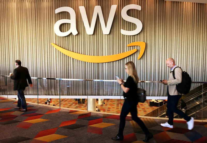 FILE PHOTO: Attendees at Amazon.com Inc annual cloud computing conference walk past the Amazon