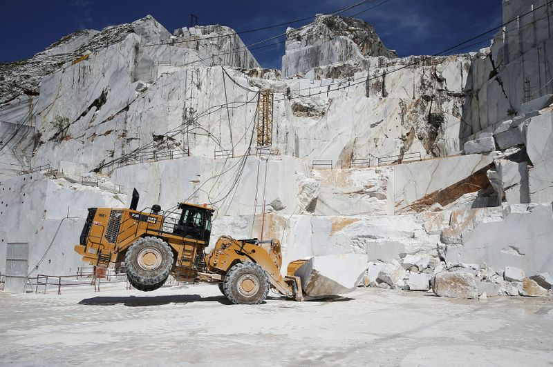 FILE PHOTO: A Caterpillar bulldozer transports a marble stone at the Cervaiole marble quarry on