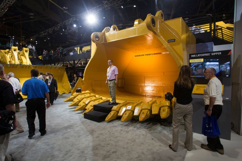 FILE PHOTO: Dmitry Golitsyn of Moscow stands in a new latchfree dipper at the Caterpillar booth