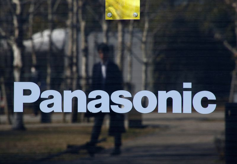 A man is reflected on Panasonic Corp's logo at Panasonic Center in Tokyo