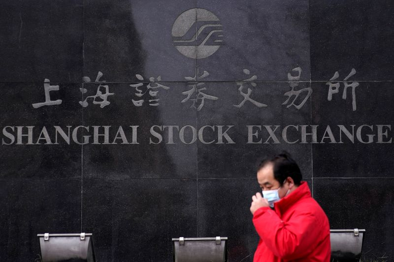 FILE PHOTO: A man wearing a mask walk at the Shanghai Stock Exchange building at the Pudong
