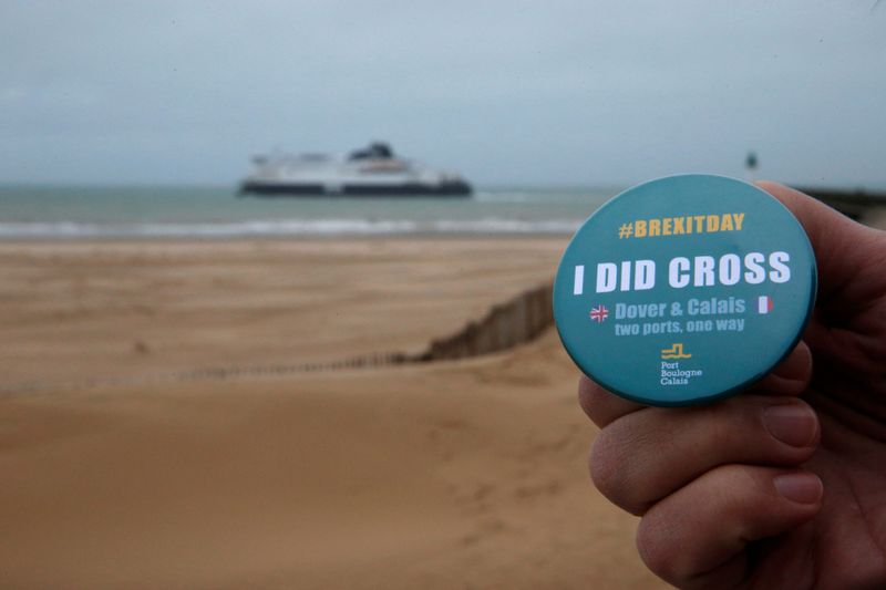 A man poses holding a badge made by the port of Boulogne Calais to mark Brexit day as P&O