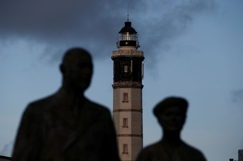 Calais lighthouse appears behind the statue of General de Gaulle and his wife in the center