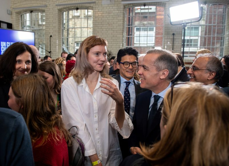 Governor of the Bank of England Mark Carney speaks with British model and actress Lily Cole