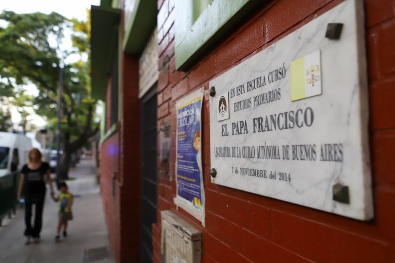 A woman and a child walk near a school where Pope Francis attended primary school when he grew