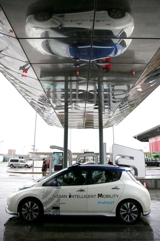 FILE PHOTO: A modified Nissan Leaf, driverless car, is reflected in an awning during a pause