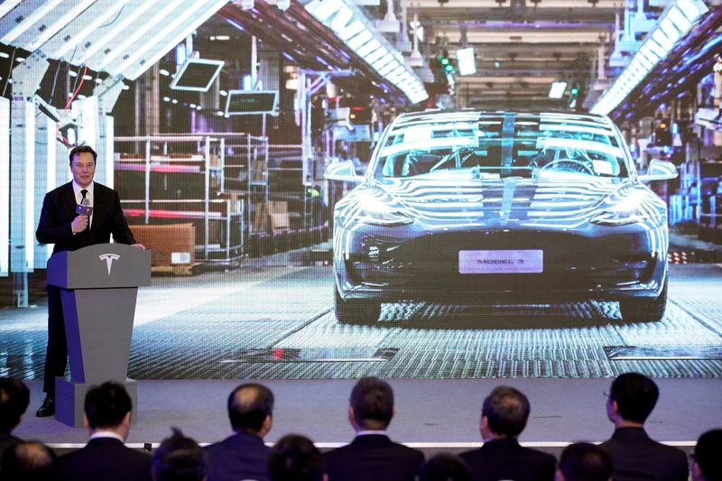 FILE PHOTO: Tesla Inc CEO Elon Musk speaks next to a screen showing an image of Tesla Model 3