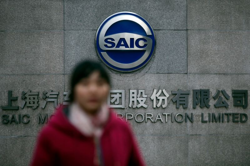 Woman walks past the gate of SAIC Motor Corporation Limited in Shanghai