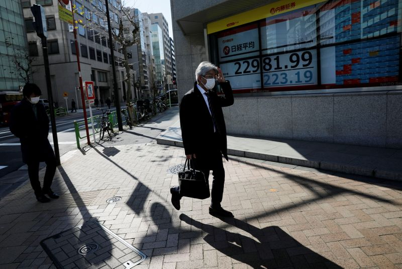 People wearing surgical masks walk past a screen showing Nikkei index outside a brokerage in