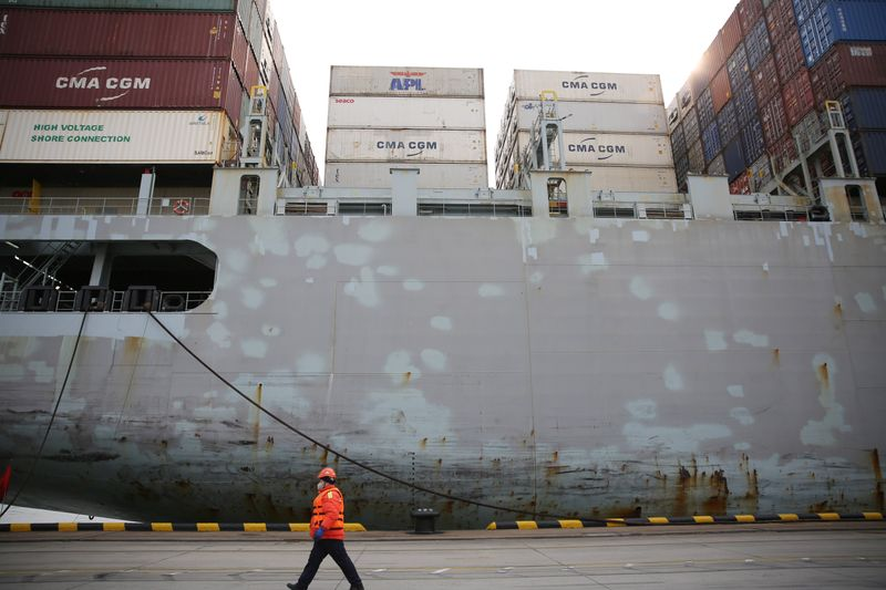 FILE PHOTO:  Worker wearing a face mask walks past a cargo ship at a container terminal of