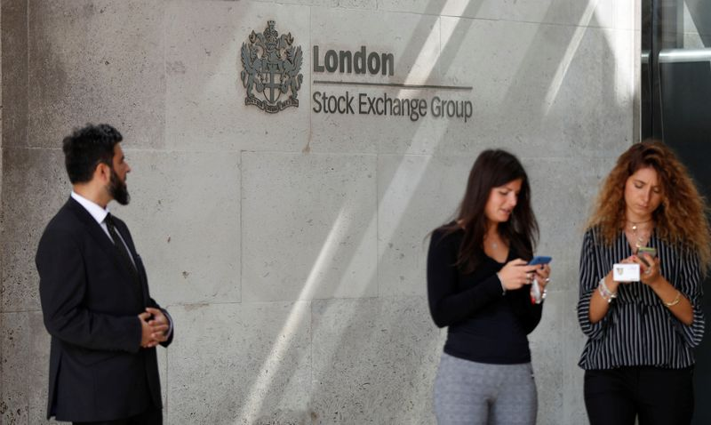 People check their mobile phones as they stand outside the entrance of the London Stock