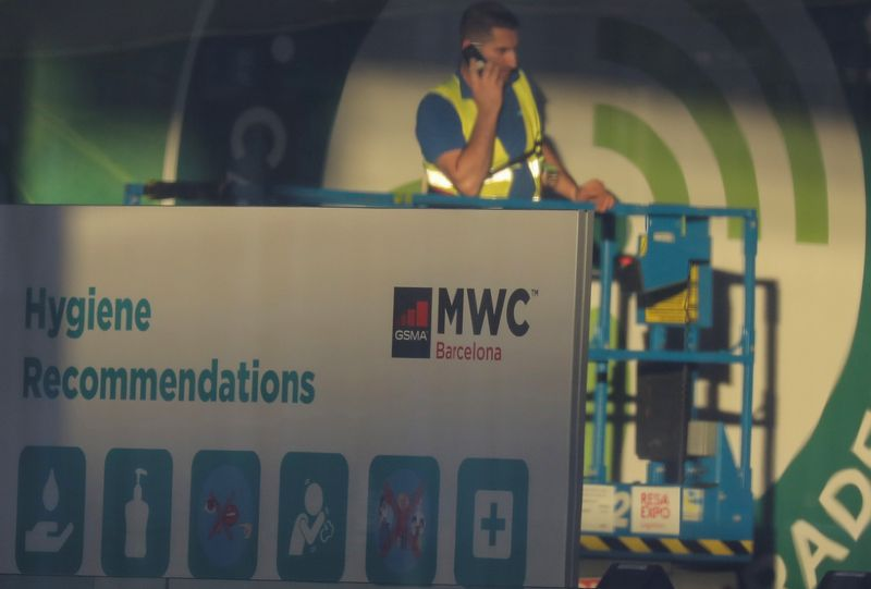 Employee is pictured next to a banner with information of MWC20 (Mobile World Congress) in